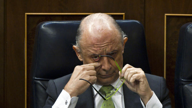 Spain's Finance Minister Cristobal Montoro scratches his face during a control session at the Spanish Parliament, in Madrid, Wednesday, June 13, 2012. The interest rate Spain would have to pay to raise money on the world's bond markets continued to rise Wednesday amid worries that a planned bank bailout might not be enough to save the country from needing an overall financial rescue. (AP Photo/Daniel Ochoa de Olza)