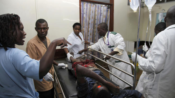 A person injured in a blast on a bus is attended to by medical staff at a hospital in Nairobi, Kenya, Sunday, Nov. 18, 2012. A Kenya police official says that an explosion on a bus in Kenya's capital has killed and injured a number of people. (AP Photo/Sayyid Azim)