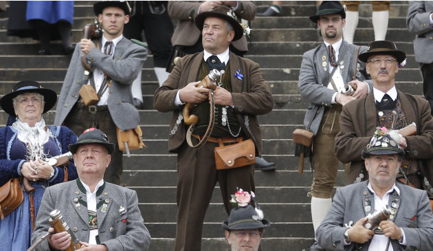 A Bavarian riflemen in traditional costume awaits to fire his muzzle loader in Munich, southern Germany, Sunday, Oct. 7, 2012. Members of various shooting clubs of the region met for a salute on the l