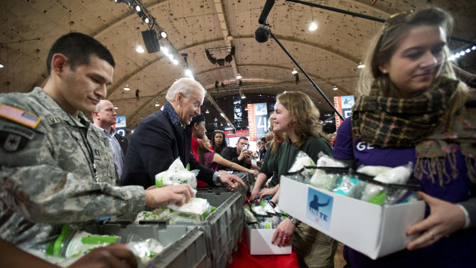 Vice President Joe Biden, center, works with volunteers, filling care kits with necessities for deployed U.S. service members, wounded warriors, veterans and first responders, joining the National Day of Service as part of the 57th presidential inauguration in Washington, Saturday, Jan. 19, 2013. Army Capt. Cesar J. Visurraga, US Army Nurse Corps, is at left.  (AP Photo/Manuel Balce Ceneta)