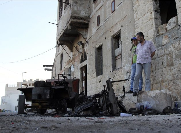 People inspect the damage after overnight clashes in Al-Koubbeh, in Tripoli