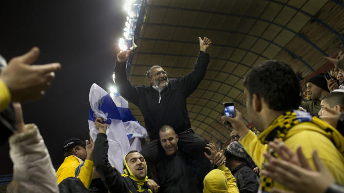 "In this Tuesday, Jan. 29, 2013 photo, Beitar Jerusalem F.C. soccer supporters lift Israeli right-wing politician Michael Ben Ari during a State Cup soccer match against Maccabi Umm al-Fahm F.C. at the Teddy Stadium in Jerusalem. Beitar has long tried to quell a tight-knit group that calls itself ""La Familia"" and whose behavior has had the team docked points and forced it to play before empty stadiums. The group is routinely abusive toward opposing players, taunting them with racist and anti-Arab chants. (AP Photo/Bernat Armangue)"