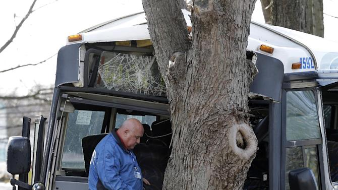 An investigator stands inside a commuter bus that crashed into a tree after colliding with a school bus Thursday, Jan. 10, 2013, in Old Bridge, N.J.  The New York City-bound commuter bus and a mini school bus crashed on a state highway in New Jersey, injuring at least 17 people, two critically.  School officials said no students were on the Old Bridge school bus, which landed on its side along Route 9.  (AP Photo/Mel Evans)