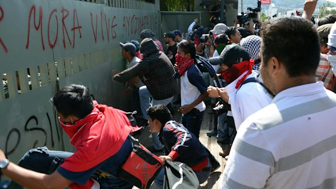 Students accompanying the relatives of 43 missing students kick the main door of a military base during a protest on the three month anniversary of the students' disappearance in Iguala, Mexico, Friday Dec. 26, 2014. Protesters threw objects, destroyed property and painted the main door of the military base to protest the army's alleged responsibility, or lack of response on the night of Sept. 26 when, according to the results of the Attorney General's investigation, the students were taken by municipal police and handed over to a drug gang, then killed and burned. (AP Photo/Alejandrino Gonzalez)