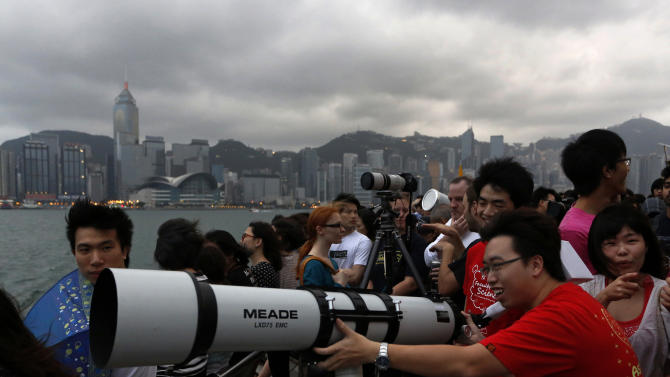 """Hong Kong stargazers use a telescope to observe an annular solar eclipse along the Victoria Habour in Hong Kong, Monday, May 21, 2012. Millions of Asians watched as a rare """"ring of fire"""" eclipse crossed their skies early Monday.  The annular eclipse, in which the moon passes in front of the sun leaving only a golden ring around its edges, was visible to wide areas across the continent.  (AP Photo/Vincent Yu)"""