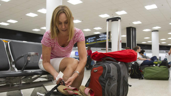 In this Friday, June 29, 2012 photo, Pat Burns, of San Diego, prepares her luggage for check-in at Miami International Airport in Miami. Burns, after an overnight stay in Miami, is traveling to the Galapagos Islands in Ecuador for the Fourth of July holiday. For the first time in five years Independence Day falls on a Wednesday, leaving travelers unsure when to celebrate and worrying those who make a living off tourists. Those who sell vacations say this year's calendar gives Americans more options: Tack on Saturday through Tuesday or Thursday through Sunday to the holiday, or just take the entire week off. (AP Photo/Alan Diaz)