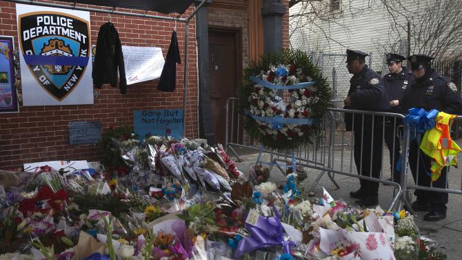 NYPD officers look on at a makeshift memorial for two officers who were fatally shot, in the Brooklyn borough of New York
