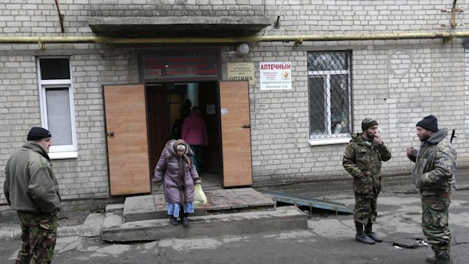 An elderly woman leaves a hospital in the town of Artemivsk, Ukraine, Thursday, Jan. 29, 2015. Fighting between government and Russian-backed separatist forces in eastern Ukraine has intensified in recent days as rebels seek to encircle the town of Debaltseve, which hosts a strategically important railway hub. (AP Photo/Petr David Josek)