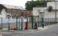 People walk past derelict buildings and a fenced off car park near the High Street in Stratford, east London on August 15, 2012. London may have basked in the euphoria of a successful Olympics in 2012 but now that the party is over, local people are wondering if its legacy can improve the deprived area which hosted the Games