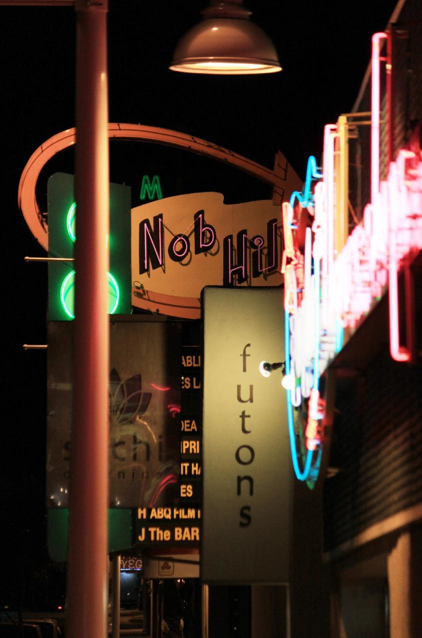In this Sept. 17, 2013 photo vintage and modern neon signs hangs above the sidewalk in the Nob Hill district along historic Route 66 in Albuquerque. A self-guided tour along this section of the route offers boutiques, restaurants and a parade of neon. (AP Photo/Susan Montoya Bryan)