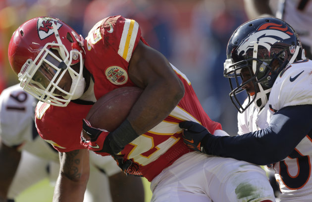 Kansas City Chiefs running back Shaun Draughn (20) is tackled by Denver Broncos strong safety Mike Adams, right, during the first half of an NFL football game at Arrowhead Stadium in Kansas City, Mo.,