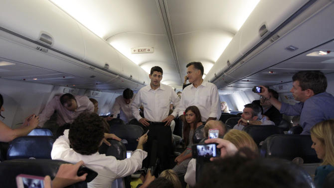 Republican presidential candidate, former Massachusetts Gov. Mitt Romney, right, and vice presidential running mate Rep. Paul Ryan R-Wis. are joined by Ronmey's granddaughter Chloe while talking to reporters on the charter flight between Virginia and North Carolina,  Saturday, Aug. 11, 2012.  (AP Photo/Mary Altaffer)