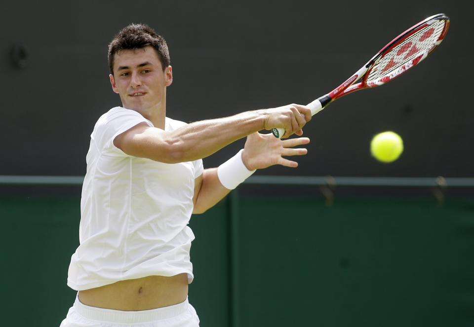 Bernard Tomic of Australia plays a return to Sam Querrey of the United States during their Men's first round singles match at the All England Lawn Tennis Championships in Wimbledon, London, Tuesday, June 25, 2013. (AP Photo/Alastair Grant)