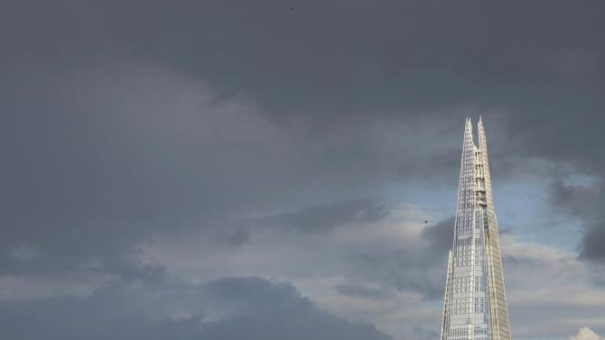 The Shard building is seen in front of dark clouds in central London