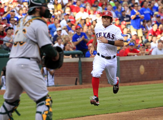 Texas Rangers' Ian Kinsler (5) heads home to score on Elvis Andrus' hit during the third inning of a baseball game against the Oakland Athletics, Sunday, July 1, 2012, in Arlington, Texas. (AP Photo/John F. Rhodes)