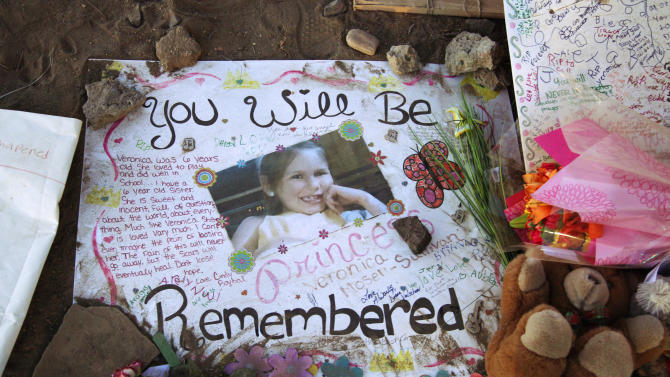 """A poster in memory of Veronica Moser-Sullivan, 6, is shown at the memorial to victims of the Aurora, Colo., movie theater shooting, Friday, July 27, 2012.  It was a week ago Friday that a gunman opened fire during a late-night showing of """"The Dark Knight Rises"""" Batman movie, killing 12 and injuring dozens of others.  Police have identified the suspected shooter as James Holmes, 24. (AP Photo/Ted S. Warren)"""