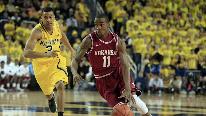 Arkansas guard BJ Young (11) drives around Michigan guard Trey Burke (3) during the first half of an NCAA college basketball game in Ann Arbor, Mich., Saturday, Dec. 8, 2012. (AP Photo/Carlos Osorio)