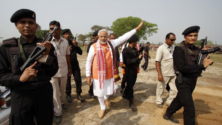 Hindu nationalist Modi is surrounded by his security personnel as he leaves after addressing an election campaign rally in Nagaon