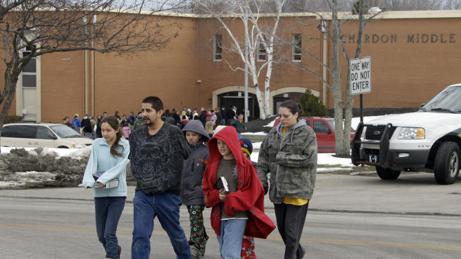 Parents take their children from Chgardon Middle School in Chardon, Ohio Monday, Feb. 27, 2012. Students were released after a gunman opened fire inside the nearby high school's cafeteria at the start of the school day Monday, wounding four students, officials said. (AP Photo/Mark Duncan)
