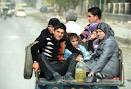 A Syrian family rides on the back of a tuc-tuc in the northern city of Aleppo on October 27. Air raids, clashes and car bombings shook Syria on Sunday, killing nearly 100 people, monitors said, as world powers look to pick up the pieces of a failed bid to bring in a Muslim holiday ceasefire