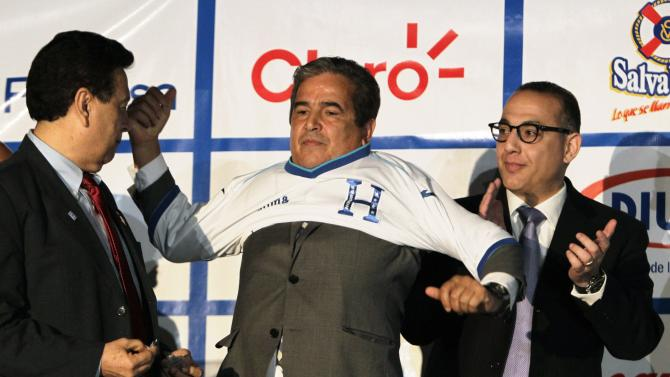 Honduras's new national soccer team head coach Pinto oputs on a team jersey during a news conference in Tegucigalpa