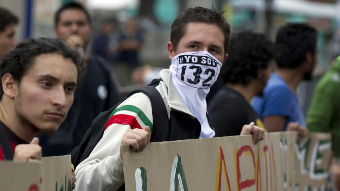 """A student of the #Yo Soy 132 or """"I am 132"""" movement wears a face mask as he demonstrates outside of the Federal Electoral Tribunal in Mexico City, Thursday, Aug. 30, 2012. Three of the seven justices on Mexico's highest election court, the Federal Electoral Tribunal, recommended Thursday dismissing legal challenges mounted by the second-place leftist candidate that seek to overturn the results of the July 1 presidential elections. The """"I am 132"""" movement began in opposition of the alleged biased coverage by the media of the 2012 elections and against the candidacy of Enrique Pena Nieto of the Revolutionary Institutional Party (PRI). (AP Photo/Eduardo Verdugo)"""
