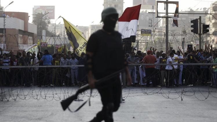 A riot police officer takes his position during a protest by members of the Muslim Brotherhood and supporters of ousted Egyptian President Mursi in Cairo