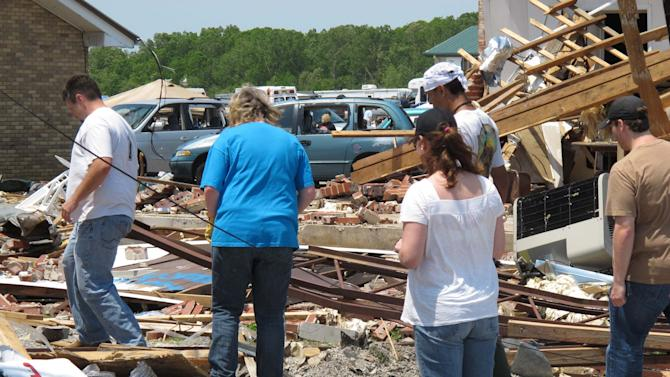 In a April 30, 2011 photo, Hackleburg Elementary School principal Joan Baker, center, carefully steps through debris, in Hackleburg, Ala. Her school was one of 18 across Alabama heavily damaged or destroyed by tornadoes. (AP Photo/Jeffrey Collins)