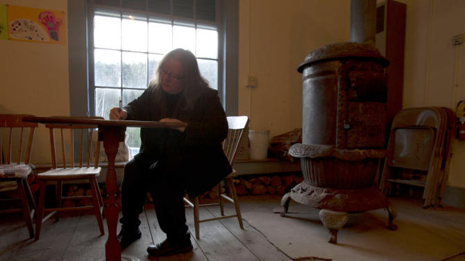 Nancy Tassey casts her ballot next to the wood stove on Election Day at the Town Hall, Tuesday, Nov. 6, 2012 in Calais, Vt. (AP Photo/Toby Talbot)