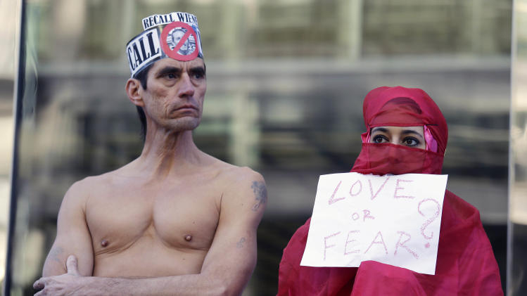 Natalie Mandeau, right, of France, holds up a sign during a demonstration against a nudity ban outside a federal building Thursday, Jan. 17, 2013 in San Francisco. Activists are asking a federal judge to block a city ordinance banning public nudity. The ban is scheduled to go into effect Feb. 1. The local law has become a divisive political issue in a town that prides itself on its inhibitions. The demonstration took place before a court hearing on the ordinance. (AP Photo/Eric Risberg)