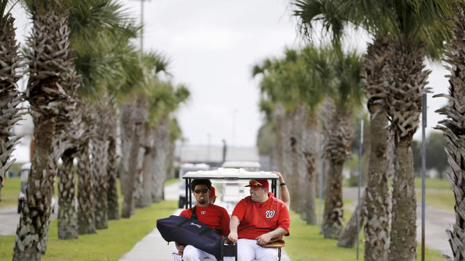 Washington Nationals' Ian Desmond, left, and batting practice pitcher Ali Modami, right, ride a golf cart back to the clubhouse following a spring training baseball workout, Sunday, March 1, 2015, in Viera, Fla. (AP Photo/David Goldman)