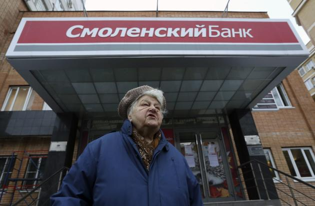 A woman speaks outside an office of Smolensky bank after she failed to get inside in Moscow