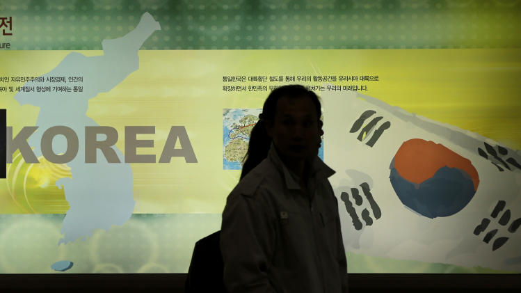 Visitors walk by a map of Korea Peninsula and South Korea's national flag at the exhibition hall of the unification observation post near the border village of Panmunjom, that has separated the two Koreas since the Korean War, in Paju, north of Seoul, South Korea, Sunday, April 7, 2013. South Korea said its top military officer has put off a plan to visit Washington due to current tension with North Korea. (AP Photo/Lee Jin-man)