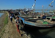 Muslim Rohingya men walk past fishing boats near the temperory relief camp at the Bawdupha on the outskirts of Sittwe, capital of Myanmar's western Rakhine state, on October 30. About 130 passengers are missing after a boat carrying Rohingya refugees sank off the border between Myanmar and Bangladesh, according to Bangladesh police and a Rohingya advocacy group on Wednesday