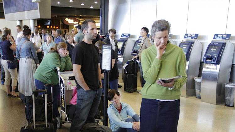 Alaska Airlines passengers wait in a long line near inoperable check-in computers, Monday, Oct. 8, 2012, at Seattle-Tacoma International Airport in Seattle during a system-wide outage of the computers the airline uses to check in passengers. (AP Photo/Ted S. Warren)