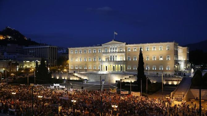 Demonstrators stand during a protest in front of the parliament in Athens