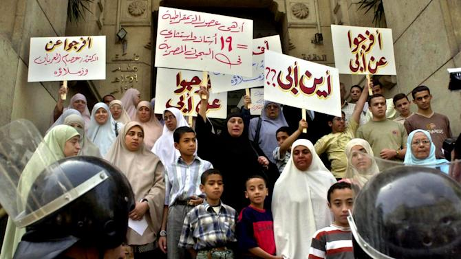 "FILE - In this Monday, May 16, 2005 file photo, Egyptian relatives of 19 detained banned Muslim Brotherhood members demonstrate in Cairo.  Arabic slogans read  ""Where is my father"", "" release my father"" and "" 19 professor at Egypt's prisons"". It was one of the most perplexing events of Egypt's 2011 revolution: Attacks on prisons that broke out more than 20,000 inmates, among them Hamas and Hezbollah militants and Muslim Brotherhood leaders, including the man who is now the country's president, Mohammed Morsi. Now a court case is trying to uncover for the first time who was behind the attacks, raising political headaches for Morsi. (AP Photo/Nasser Nouri, File)"
