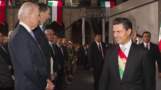 Newly sworn-in Mexico's President Enrique Pena Nieto walks past a line of visiting dignitaries including U.S. Vice President Joe Biden, left, as he leaves the National Palace after delivering his inaugural speech in Mexico City, Saturday, Dec. 1, 2012. Protesters opposed to the new president clashed with tear gas-wielding police early Saturday morning outside the National Congress, where Pena Nieto took the oath of office. (AP Photo/Christian Palma)