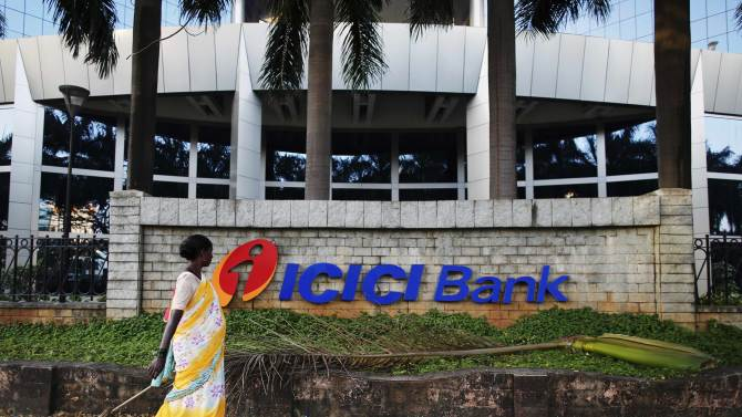 A municipal worker walks past a logo of ICICI Bank at its headquarters in Mumbai