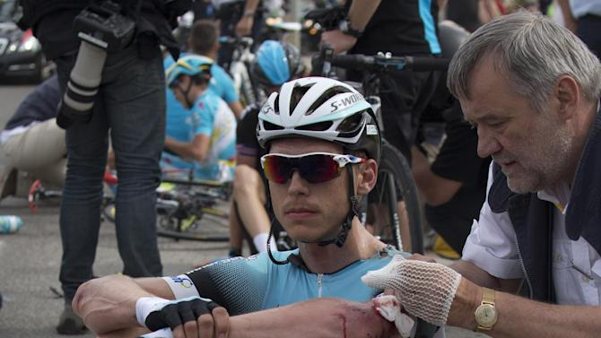 A doctor tends to Tony Martin of Germany after he crashed in the first stage of the Tour de France cycling race over 213 kilometers (133 miles) with start in Porto Vecchio and finish in Bastia, Corsica island, France, Saturday June 29, 2013. (AP Photo/Joel Saget, POOL)
