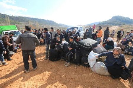 Internally displaced Syrians fleeing advancing pro-government Syrian forces wait near the Syrian-Turkish border after they were given permission by the Turkish authorities to enter Turkey, in Khirbet Al-Joz