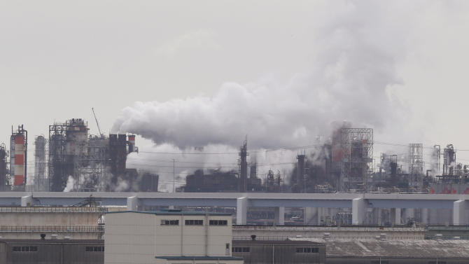 In this Monday, Oct. 21, 2013 photo, smoke billows from an oil refinery in Kawasaki, southwest of Tokyo. Japan has drastically scaled back its target for reducing greenhouse gas emissions, complicating efforts to forge a global climate change pact.The new target approved by the Cabinet on Friday, Nov 15 calls for reducing emissions by 3.8 percent from their 2005 level by 2020. The revision was necessary because the earlier goal of a 25 percent reduction from the 1990 level was unrealistic, the chief government spokesman, Yoshihide Suga, told reporters in Tokyo. (AP Photo/Koji Sasahara)