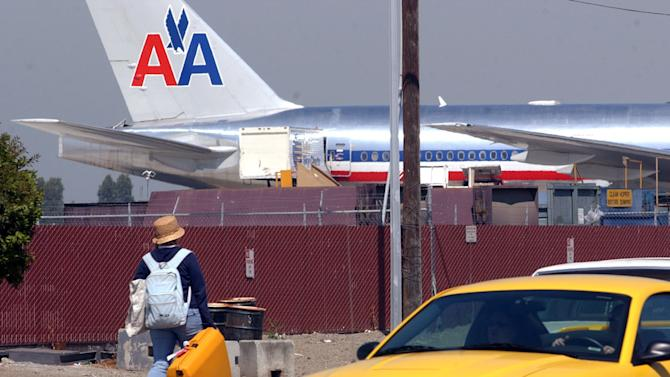File- This July 2, 2004, file photo shows a traveler walking from one terminal to another at San Jose Airport in San Jose, Calif. FBI officials say a 16-year-old boy stowed away in the wheel well of a flight from California to Hawaii, surviving the trip halfway across the Pacific Ocean unharmed despite frigid. Security footage from the San Jose airport verified that the boy hopped a fence to get to Hawaiian Airlines Flight 45 on Sunday April 20, 2014. (AP Photo/Paul Sakuma, File)