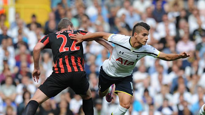 Tottenham Hotspur's Erik Lamela (R) takes the ball off Queens Park Rangers' Richard Dunne during the match at White Hart Lane in north London on August 24, 2014