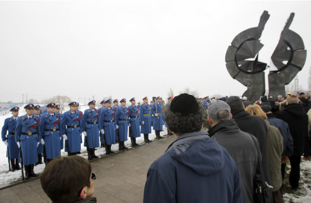 Serbian military honor guards stand to attention as people attend commemorations for victims of the Holocaust at a monument erected in the former World War II Nazi concentration camp of Sajmiste in Be