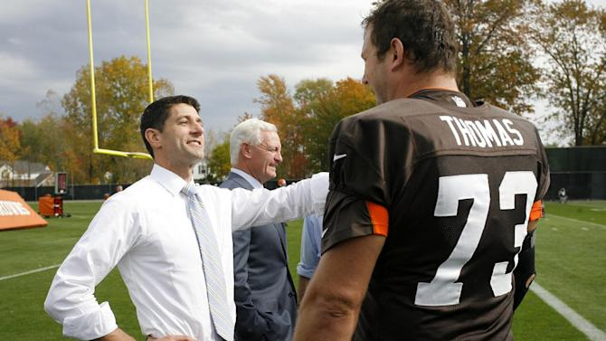 """FILE - This Oct. 17, 2012 file handout photo provided by the Cleveland Browns shows Republican vice presidential candidate Rep. Paul Ryan, R-Wis., left, accompanied by new Cleveland Browns' football team owner Jimmy Haslam, center, visiting with Cleveland Browns offensive tackle Joe Thomas at the NFL team's practice facility in Berea, Ohio. In a rare show of unity, President Barack Obama and challenger Mitt Romney took turns praising Washington Redskins rookie quarterback Robert Griffin III a couple of weeks ago for a video that aired on the Fox network NFL pregame show. They uttered polished, rote lines such as Romney's """"RG3 hasn't been in Washington very long, but he's already created change"""" and Obama's """"You're welcome at my house for a pickup game anytime.""""  (AP Photo/John Reid, Cleveland Browns, File)"""