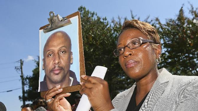 Fulton County Police public information officer Kay Lester holds up the picture of Floyd Palmer, the suspect being sought in a fatal shooting at World Changers Church International in College Park, Ga. Wednesday, Oct. 24, 2012. A church volunteer leading prayer was shot and killed inside the chapel of the megachurch. (AP Photo/Atlanta Journal-Constitution, John Spink)  MARIETTA DAILY OUT; GWINNETT DAILY POST OUT; LOCAL TV OUT; WXIA-TV OUT; WGCL-TV OUT