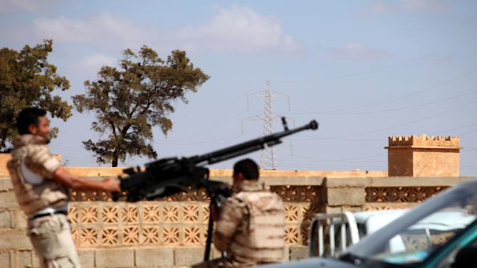 Soldiers from the Libyan National Army  get ready to enter  Rafallah al-sahati Islamic Militia Brigades compound, one of the compound buildings which can be seen behind the wall, in Benghazi, Libya, Saturday, Sept. 22, 2012.  On Friday evening hundreds of protesters angry over last week's killing of the U.S. ambassador to Libya stormed the compound of the Islamic extremist Ansar al-Shariah Brigade militia suspected in the attack, evicting militiamen and setting fire to their building. After taking over the Ansar compound, protesters then drove to attack the Benghazi headquarters of Rafallah Sahati where militiamen opened fire on the protesters, who were largely unarmed leaving at least 20 wounded, and several killed according to hospital sources. (AP Photo/Mohammad Hannon)