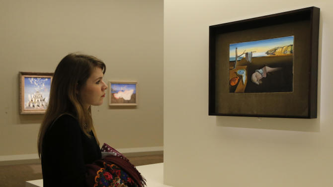 "In this photo taken Monday Nov. 19, 2012, a visitor looks at the painting 'La Persistance de la Memoire, 1931', by Spanish artist Salvador Dali (1904-1989) during the presentation to the press of the exhibition ""Dali"" at the Centre Pompidou modern art museum, in Paris. A major retrospective of Salvador Dali in Paris aims to rewrite the art history books, reconciling for the first time the last decades of his life _ when he was accused of money-making self-publicity through numerous television appearances _ with his earlier, respected Surrealist period. (AP Photo/Francois Mori)"