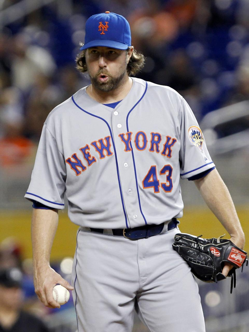 New York Mets R.A. Dickey prepares to pitch after Miami Marlins' Carlos Lee hit a single driving in Jose Reyes during the sixth inning of a baseball game in Miami, Tuesday, Oct. 2, 2012. (AP Photo/Alan Diaz)